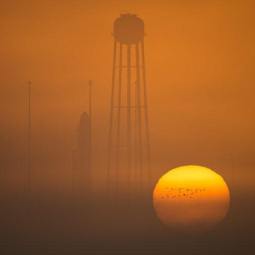 The sun rises behind the Antares rocket standing tall atop its Wallops Island Launch Pad - Photo: NASA/Bill Ingalls