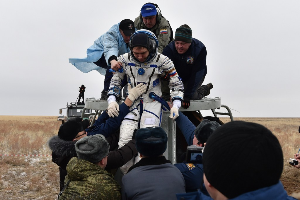 Ground personnel help International Space Station (ISS) crew member Sergei Volkov of Russia to get off the Soyuz TMA-18M space capsule after landing near the town of Dzhezkazgan, Kazakhstan, on March 2, 2016. US astronaut Scott Kelly and Russian cosmonaut Mikhail Kornienko returned to Earth on March 2 after spending almost a year in space in a ground-breaking experiment foreshadowing a potential manned mission to Mars. AFP PHOTO / POOL / KIRILL KUDRYAVTSEV