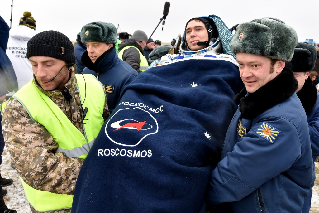 Ground personnel carry International Space Station (ISS) crew member Sergei Volkov of Russia after landing near the town of Dzhezkazgan, Kazakhstan, on March 2, 2016. US astronaut Scott Kelly and Russian cosmonaut Mikhail Kornienko returned to Earth on March 2 after spending almost a year in space in a ground-breaking experiment foreshadowing a potential manned mission to Mars. AFP PHOTO / POOL / KIRILL KUDRYAVTSEV