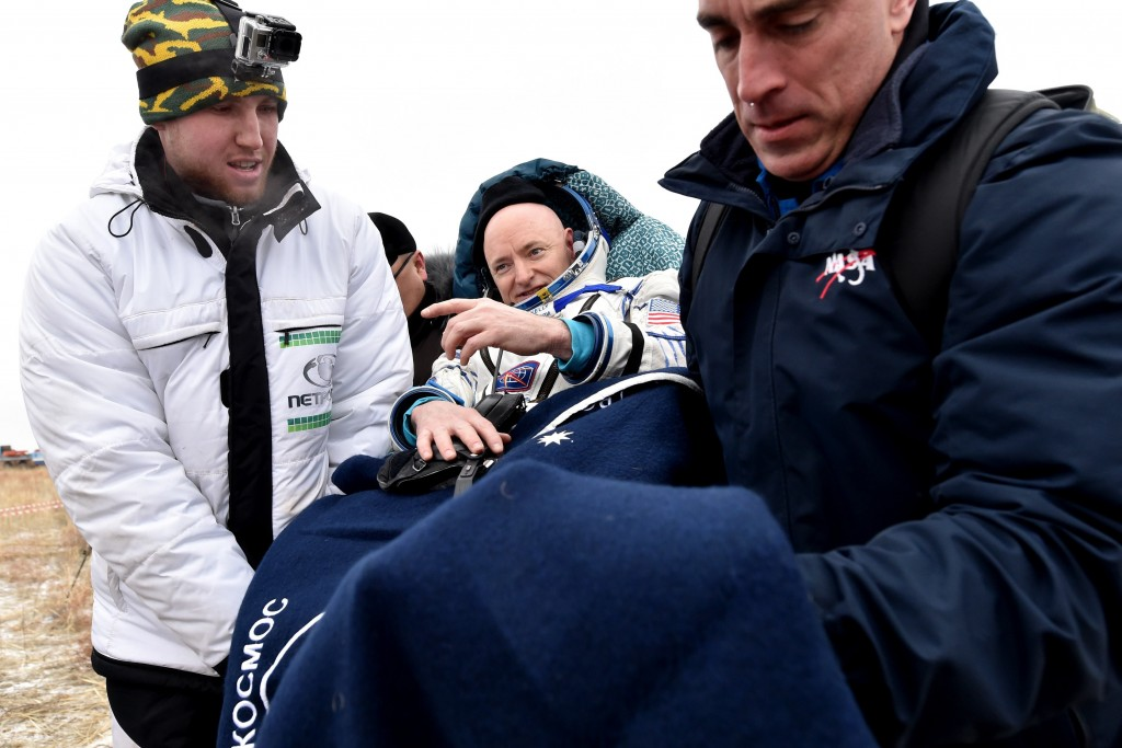 Ground personnel carry International Space Station (ISS) crew member Scott Kelly of the U.S. after landing near the town of Dzhezkazgan, Kazakhstan, on March 2, 2016. US astronaut Scott Kelly and Russian cosmonaut Mikhail Kornienko returned to Earth on March 2 after spending almost a year in space in a ground-breaking experiment foreshadowing a potential manned mission to Mars. AFP PHOTO / POOL / KIRILL KUDRYAVTSEV