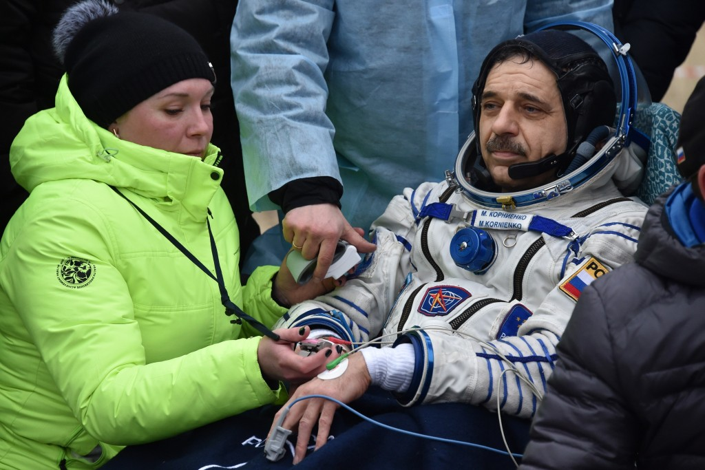 Medics check International Space Station (ISS) crew member Mikhail Kornienko of Russia after landing near the town of Dzhezkazgan, Kazakhstan, on March 2, 2016. US astronaut Scott Kelly and Russian cosmonaut Mikhail Kornienko returned to Earth on March 2 after spending almost a year in space in a ground-breaking experiment foreshadowing a potential manned mission to Mars. AFP PHOTO / POOL / KIRILL KUDRYAVTSEV