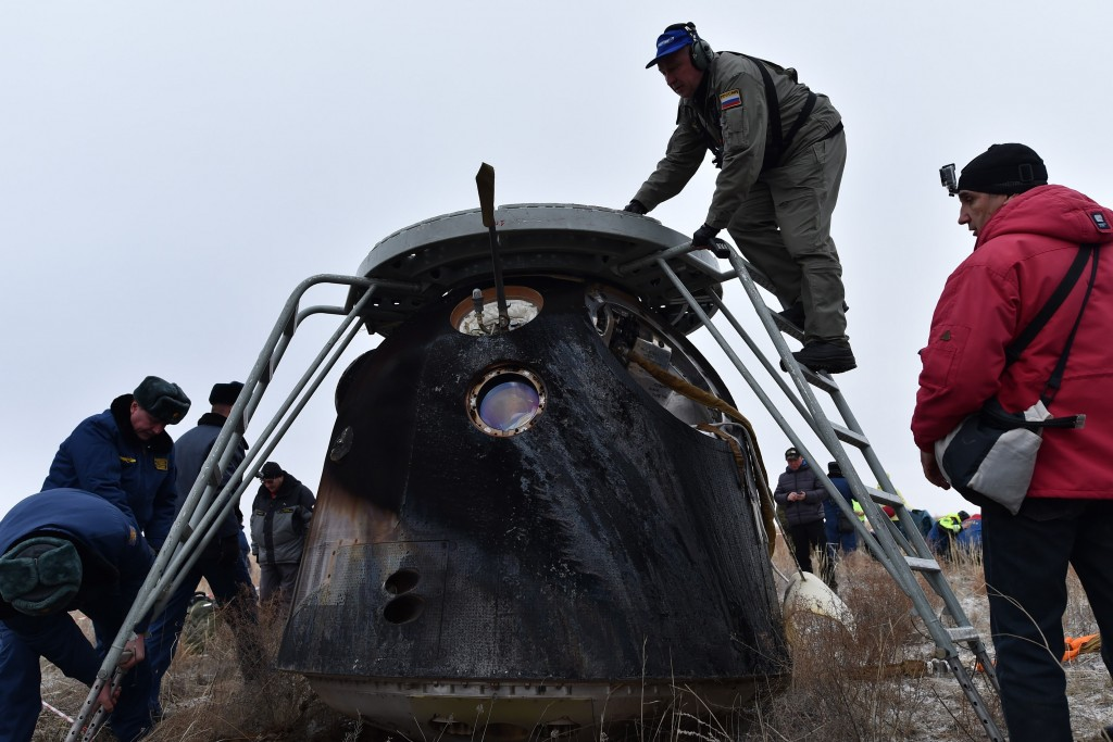 A search and rescue team works at the site of landing of the Soyuz TMA-18M space capsule carrying the International Space Station (ISS) crew of US astronaut Scott Kelly and Russian cosmonauts Mikhail Kornienko and Sergei Volkov outside the town of Dzhezkazgan, Kazakhstan, on March 2, 2016. US astronaut Scott Kelly and Russian cosmonaut Mikhail Kornienko returned to Earth on March 2 after spending almost a year in space in a ground-breaking experiment foreshadowing a potential manned mission to Mars. AFP PHOTO / POOL / KIRILL KUDRYAVTSEV