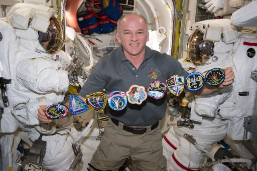 Jeff Williams pictured inside the Station's Quest Airlock with patches from his two-decade spaceflight career – Photo: NASA