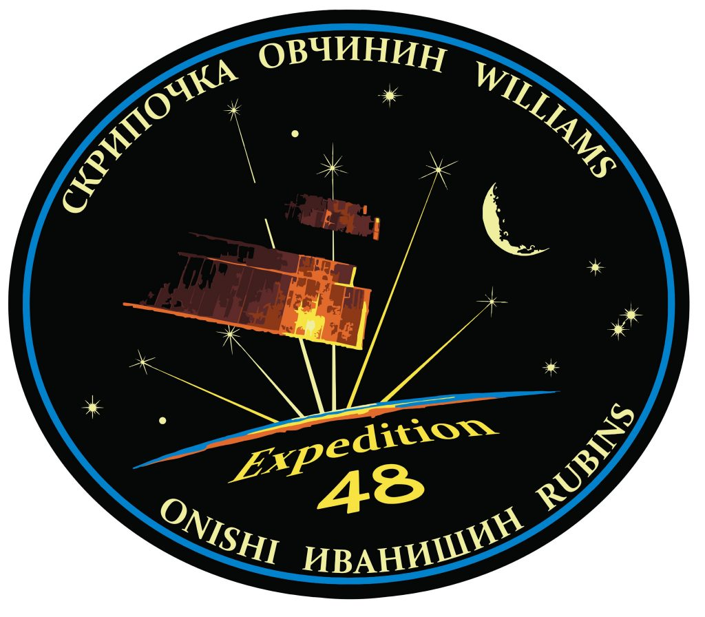 The Expedition 48 Crew Patch depicts the iconic solar arrays of the International Space Station glowing in the sunlight with a star-filled sky, the Moon and Earth's backlit limb in the background, showing the thin atmosphere protecting planet Earth. Six stars connected to the glowing sunlight represent the six Expedition 48 crew members. -- Credit: NASA