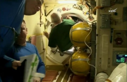 Jeff Williams and Oleg Skripochka float into their Soyuz spacecraft - Photo: NASA TV