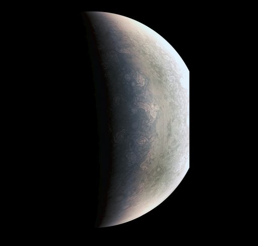 This enhanced photo of Jupiter's north pole, taken from a distance of 78,000km, brings out a boundary between the grayish region closer to the pole (left) and a lighter-toned area to the south. This boundary may be the result of a different in temperature between the atmospheric zone near the pole and toward the equator. The darker region near the pole is littered with storms that will a focus of Juno's scientific mission. - Credit: NASA/JPL-Caltech/SwRI/MSSS