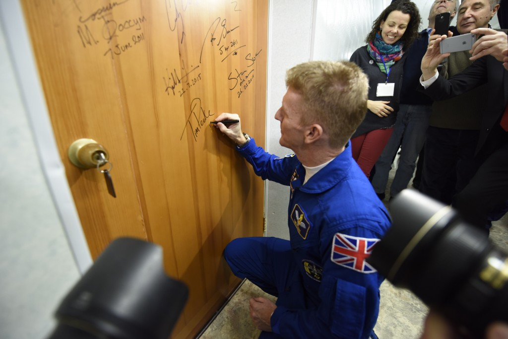 Tim_Peake_performs_the_traditional_door_signing_at_the_Cosmonaut_Hotel