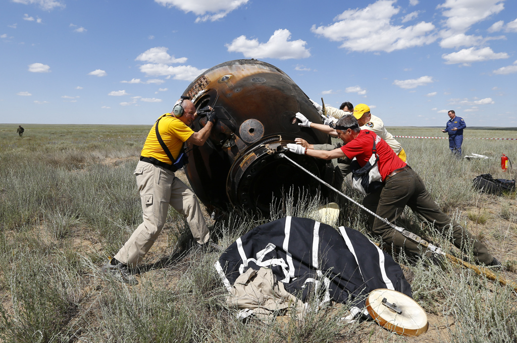 Search and rescue team members roll Soyuz TMA-19M spacecraft capsule carrying ISS crew members Peake of Britain, Malenchenko of Russia and Kopra of U.S. shortly after landing Dzhezkazgan